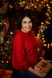 De zwangere meisjeszitting met stelt bij een Kerstboom voor stock fotografie