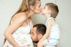 De zwangere moeder, de vader en de zoon kussen Stock Afbeelding
