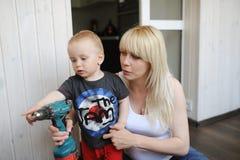 De zwangere moeder toont aan de kleine zoon het hulpmiddel voor hardhandig optreden stock foto