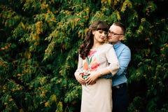 De zwangere mooie vrouw en haar het knappe echtgenoot mooie ontspannen op aard, hebben picknick in de herfstpark Royalty-vrije Stock Afbeeldingen
