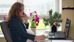 De zwangere secretaressevrouw maakt telefoongesprek en spanning na het stock videobeelden