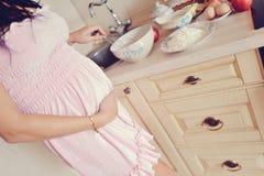 De zwangere vrouw bereidt ontbijt voor stock afbeelding