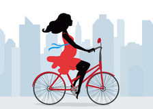 De zwangere vrouw berijdt een Fiets op de achtergrond van de stad Royalty-vrije Stock Foto