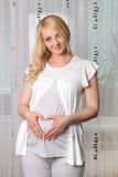 De zwangere vrouw bevindt zich Royalty-vrije Stock Foto's