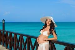 De zwangere vrouw bevindt zich op een houten pijler op de achtergrond van het overzees Dominicaanse Republiek, de Caraïbische Zee Royalty-vrije Stock Fotografie
