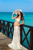 De zwangere vrouw bevindt zich op een houten pijler op de achtergrond van het overzees Dominicaanse Republiek, de Caraïbische Zee Stock Foto's