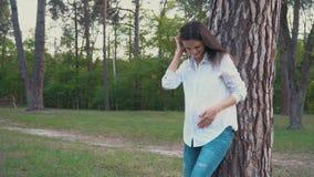 De zwangere vrouw die haar buik houden lopend onder de zomer probeert stock video
