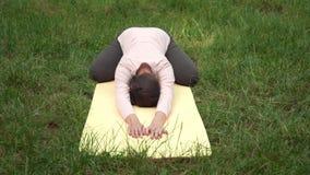 De zwangere vrouw die yoga in het park op het tapijt doen, die in doen stelt van een ijsbeer stock video