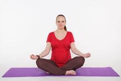 De zwangere vrouw doet yoga en het mediteren Royalty-vrije Stock Fotografie