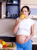 De zwangere vrouw drinkt het jus d'orange Stock Afbeeldingen