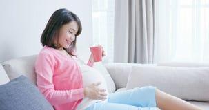 De zwangere vrouw drinkt thee stock foto