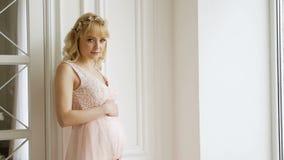 De zwangere vrouw in een lange kleding bevindt zich bij het grote venster stock videobeelden
