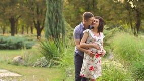 De zwangere vrouw en haar echtgenoot lopen in park stock video