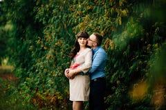 De zwangere vrouw en haar het knappe echtgenoot mooie koesteren op aard, hebben picknick in park Royalty-vrije Stock Foto