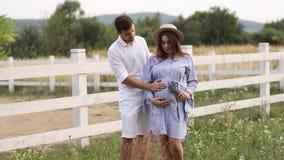 De zwangere vrouw en de man koesteren elkaar en tonen hun liefde Paar die op babymeisje wachten video stock footage
