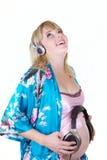 De zwangere vrouw het luisteren muziek isoleert stock afbeeldingen
