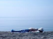 De zwangere vrouw ligt op het strand Royalty-vrije Stock Foto's