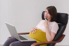 De zwangere vrouw maakt een aankoop op Internet royalty-vrije stock foto