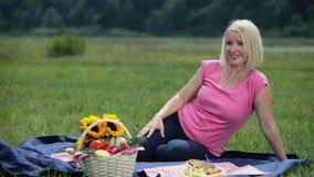 De zwangere vrouw merkt ver weg een persoon op en nodigt haar over aan picknick uit stock videobeelden
