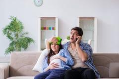 De zwangere vrouw met echtgenoot thuis Royalty-vrije Stock Afbeelding