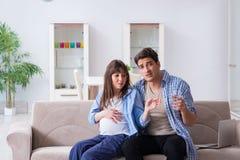 De zwangere vrouw met echtgenoot thuis Stock Foto