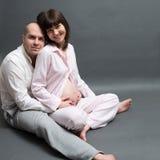 De zwangere vrouw met echtgenoot wat betreft buik, gelukkige ouders denkt Stock Afbeeldingen