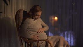 De zwangere vrouw met lange haartijd voelde eerst de beweging binnen van haar baby De dame is gelukkig en opgewekt stock video