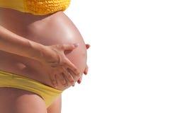 De zwangere vrouw met overhandigt buik Stock Fotografie