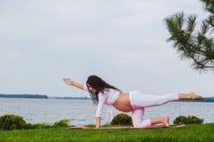 De zwangere vrouw oefent yoga naast rivier uit royalty-vrije stock fotografie