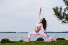 De zwangere vrouw oefent yoga naast rivier uit royalty-vrije stock afbeelding