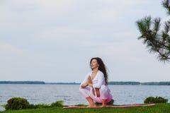 De zwangere vrouw oefent yoga naast rivier uit stock afbeeldingen