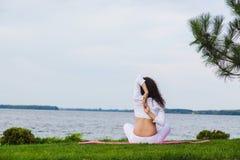 De zwangere vrouw oefent yoga naast rivier uit royalty-vrije stock afbeeldingen