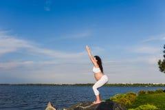 De zwangere vrouw oefent yoga naast rivier uit stock foto's