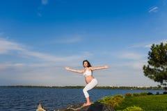 De zwangere vrouw oefent yoga naast rivier uit royalty-vrije stock foto