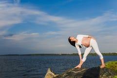 De zwangere vrouw oefent yoga naast rivier uit stock afbeelding