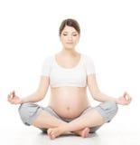 De zwangere vrouw ontspant het doen van yoga, zittend in lotusbloempositie Stock Foto's