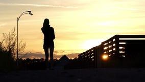 De zwangere vrouw roept haar echtgenoot bij een aardige zonsondergang in slo-mo stock footage