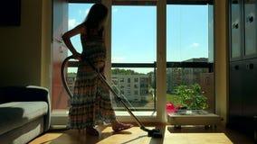De zwangere vrouw van de huisbewaarder met grote buik hoover ruimte met stofzuiger stock videobeelden