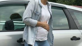 De zwangere vrouw voelt samentrekkingen, die naar ziekenwagen door auto, voorbarige geboorte gaan stock video