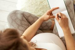De zwangere vrouw wordt klaar voor het moederschapsziekenhuis, inpakkend babymateriaal Zwangerschap, geboorteconcept royalty-vrije stock foto's