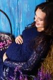 De zwangere vrouw zit met hooi en bloemen Royalty-vrije Stock Afbeelding