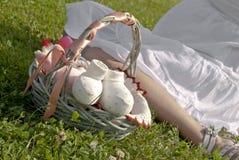 De zwangere vrouw zit op het gras Royalty-vrije Stock Afbeeldingen