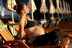 De zwangere vrouw zonnebaadt stock foto's