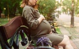 De zwangere vrouwenzitting in het park, sluit omhoog van de buik stock fotografie