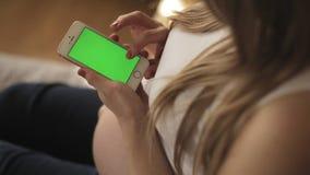 De zwangere zitting van de blondevrouw op bank die smartphone met het groene scherm gebruiken stock videobeelden
