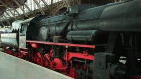 De zware industriële rode en zwarte de motorwielen van de stoom voortbewegingstrein is bij het station stock footage