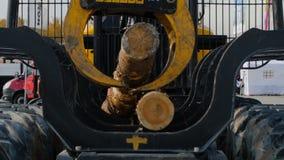 De zware materiaallading met clipper sneed logboeken De grote de logboeklader en verrichtingen in de logboekwerf bij een naaldboo stock foto's