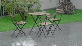 De zware regen stompt in de binnenplaats en op het natte meubilair Een lijst en klusjes arewet stock video