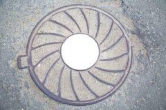 De zware sering van het mangatgietijzer met een patroon van uiteenlopende stralen op de achtergrond van grijs asfalt In het centr royalty-vrije stock fotografie