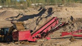 De zware tractorwerken in een zand hakken uit stock video